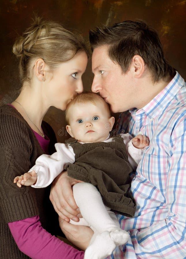 Pares que besan al bebé fotografía de archivo libre de regalías