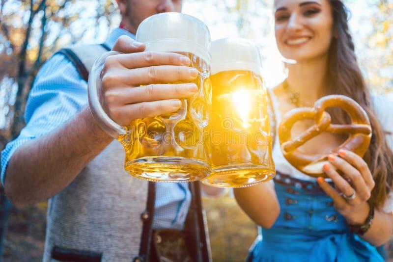 Pares que brindam com cerveja em Baviera foto de stock