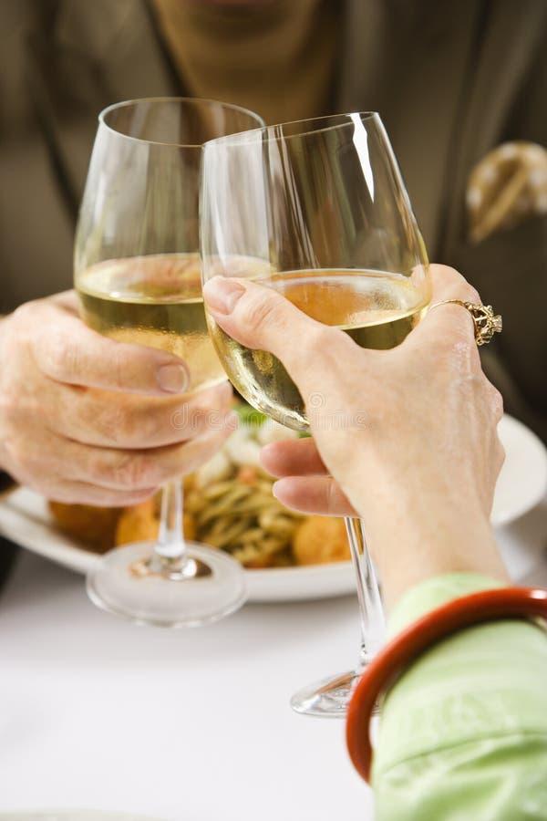 Pares que brindam o vinho. imagens de stock royalty free