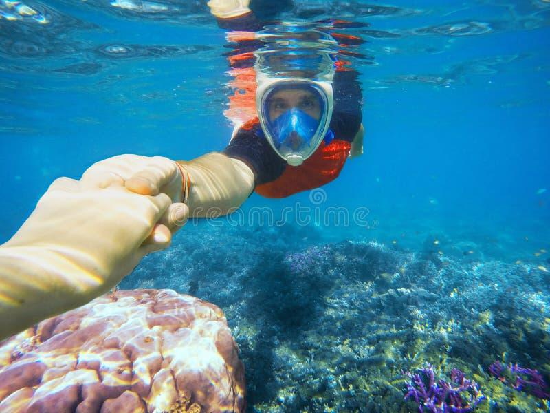 Pares que bucean que llevan a cabo las manos en el océano azul cerca del arrecife de coral imagenes de archivo