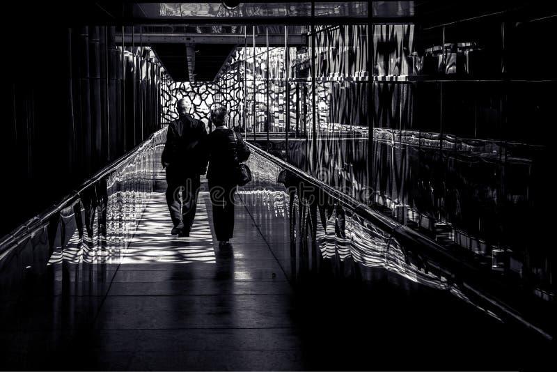 Pares que caminan abajo del pasillo puesto en contraste fotos de archivo