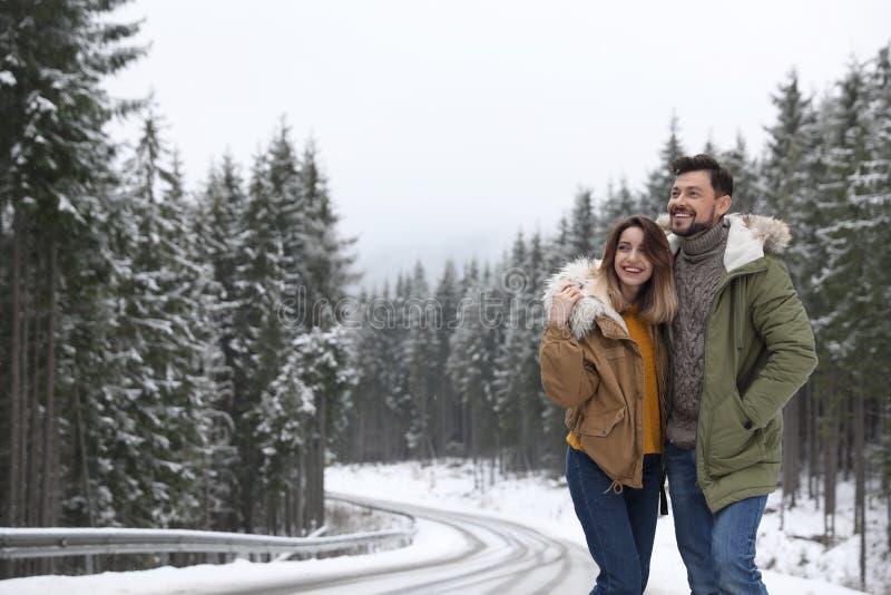 Pares que caminan cerca del bosque nevoso, espacio para el texto Invierno imágenes de archivo libres de regalías