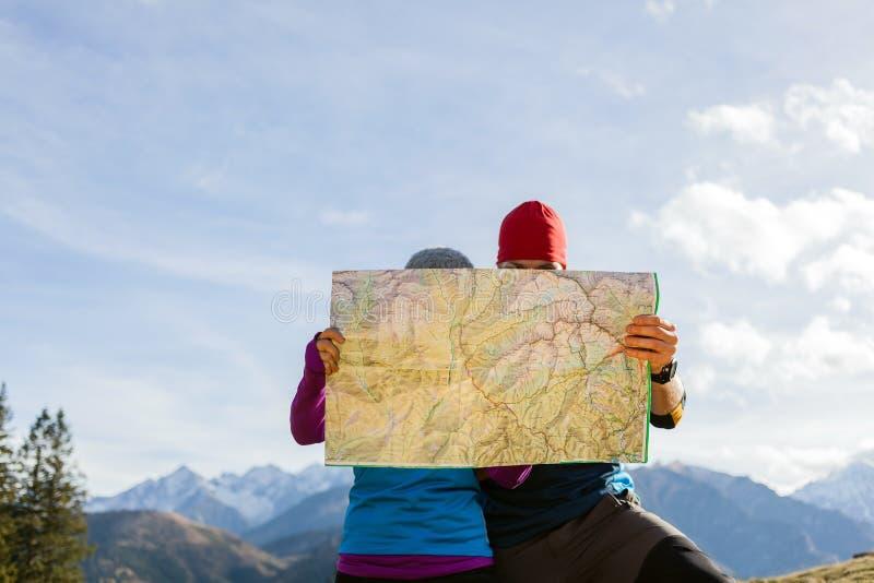 Pares que caminan con el mapa en montañas imagen de archivo