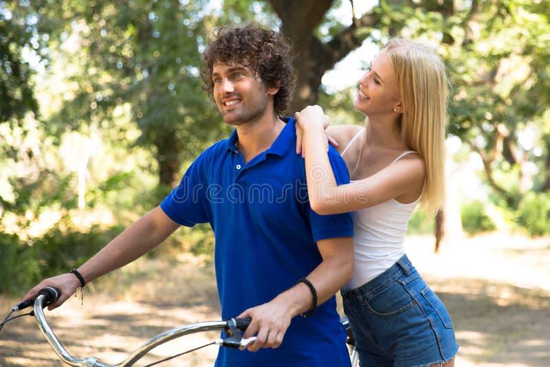 Pares que caminan con la bicicleta al aire libre en parque fotos de archivo libres de regalías