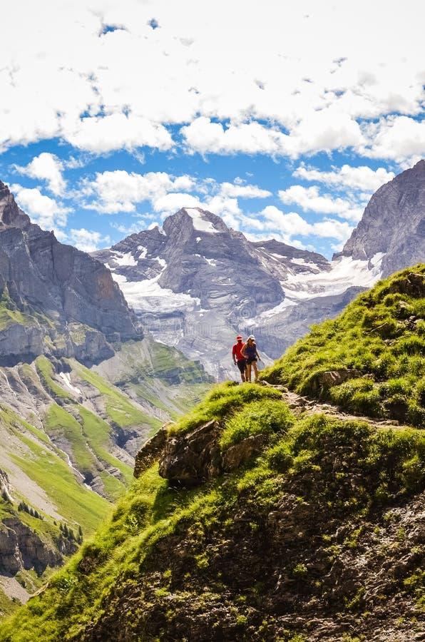 Pares que caminan en caminar la trayectoria en las montañas capturadas en la foto vertical Altas montañas coronadas de nieve en f imagen de archivo