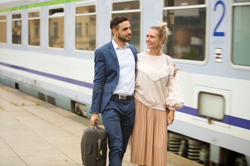 Pares que caminan en la plataforma al lado de un tren fotografía de archivo libre de regalías