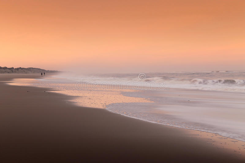 Pares que caminan en una playa en la puesta del sol fotografía de archivo libre de regalías