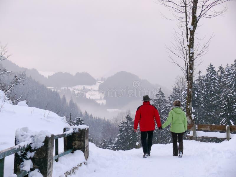 Pares que caminan en una trayectoria nevosa de la montaña foto de archivo libre de regalías