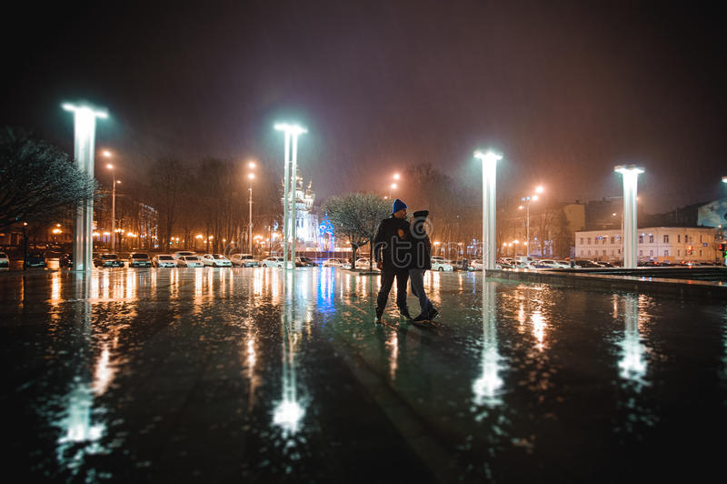 Pares que caminan a través de ciudad junto en la noche imagen de archivo libre de regalías
