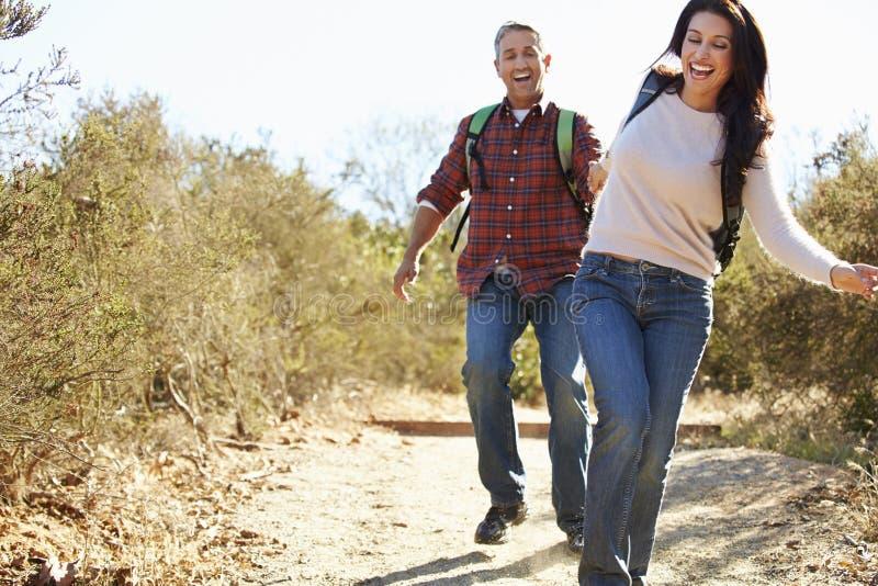Pares que caminham em umas trouxas vestindo do campo fotografia de stock royalty free