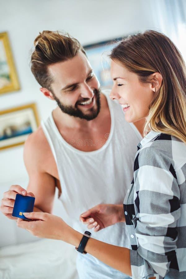 Pares que celebran la tarjeta y la sonrisa de crédito foto de archivo