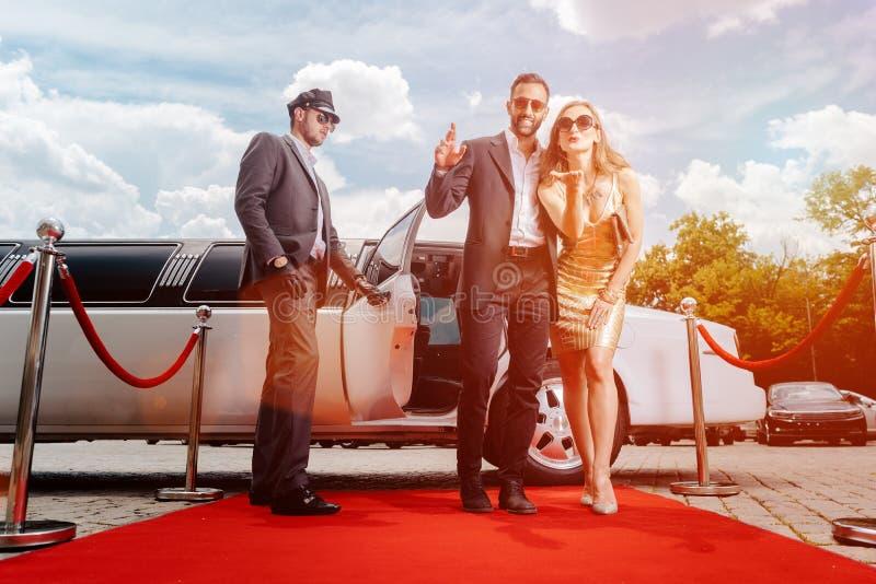 Pares que chegam com tapete vermelho de passeio da limusina imagem de stock royalty free