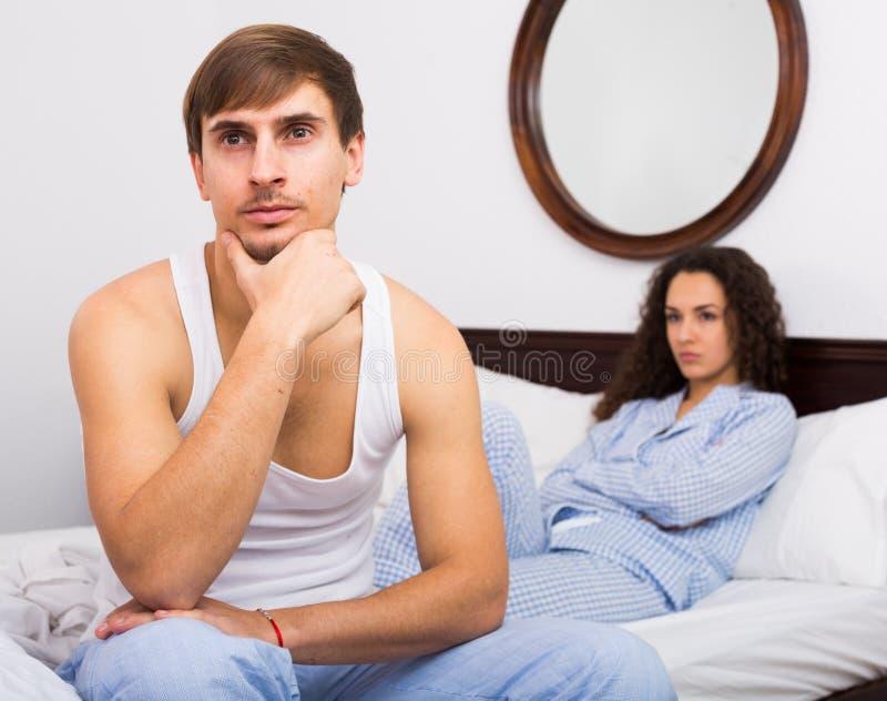 Pares que classificam para fora relacionamentos na cama imagens de stock