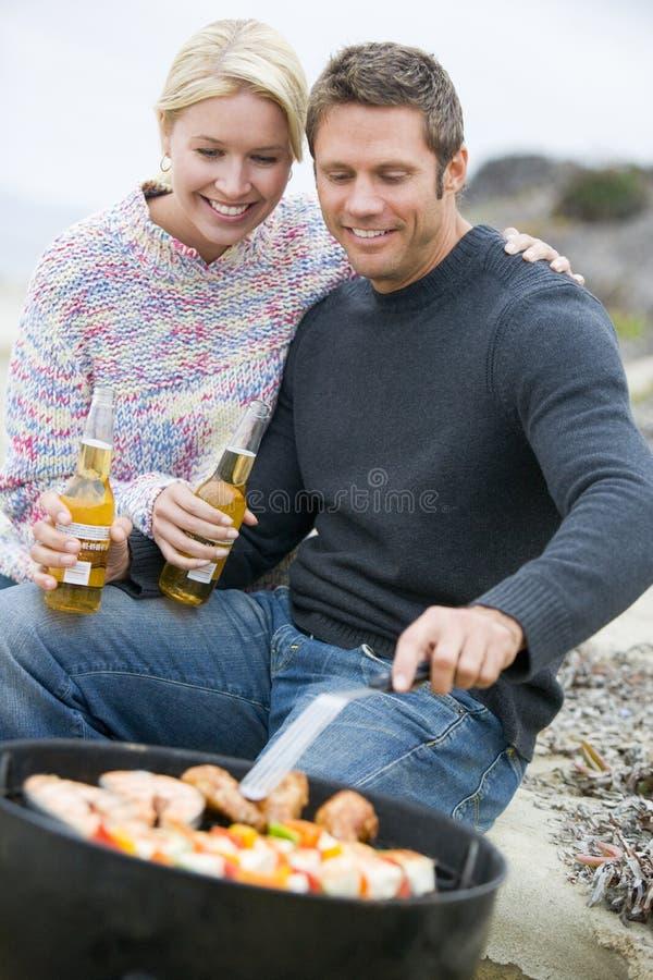 Pares que cocinan la barbacoa en la playa de A fotos de archivo