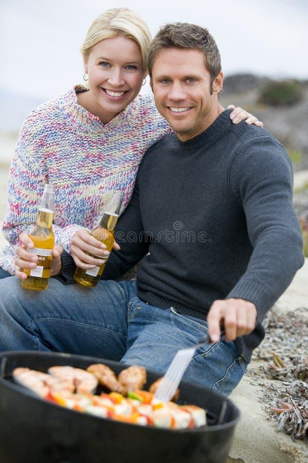 Pares que cocinan la barbacoa en una playa imagen de archivo