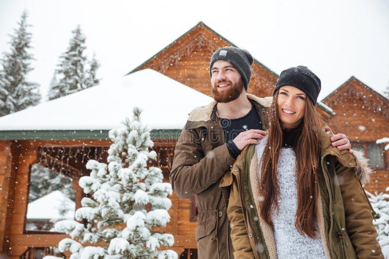 Pares que colocan la cabaña de madera cercana en tiempo nevoso imagenes de archivo