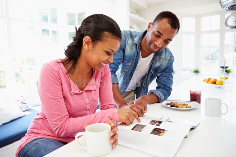 Pares que comem o café da manhã e que leem o compartimento na cozinha fotografia de stock