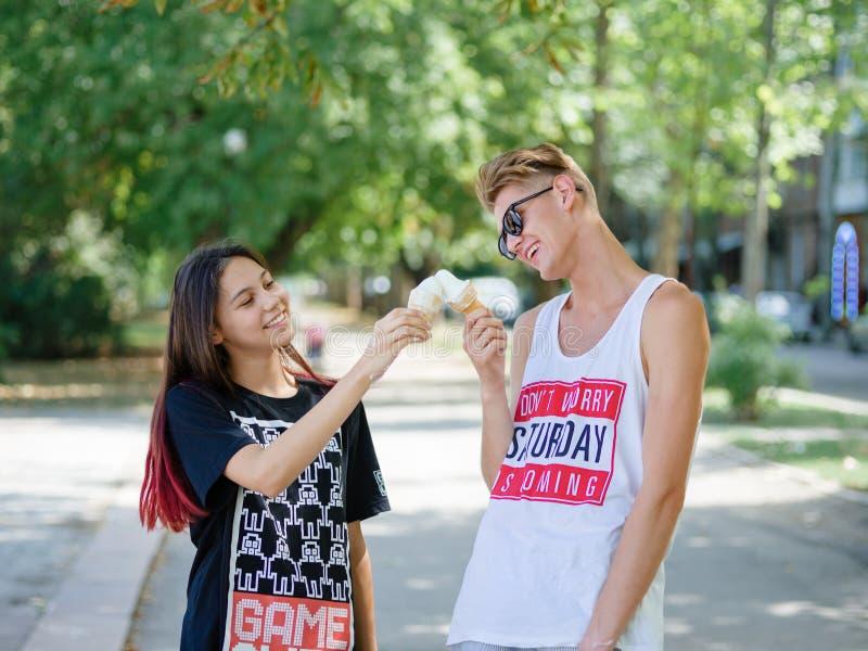 Pares que comem o gelado em um parque Noivo e amiga em um fundo natural borrado Datando o conceito Copie o espaço fotografia de stock royalty free