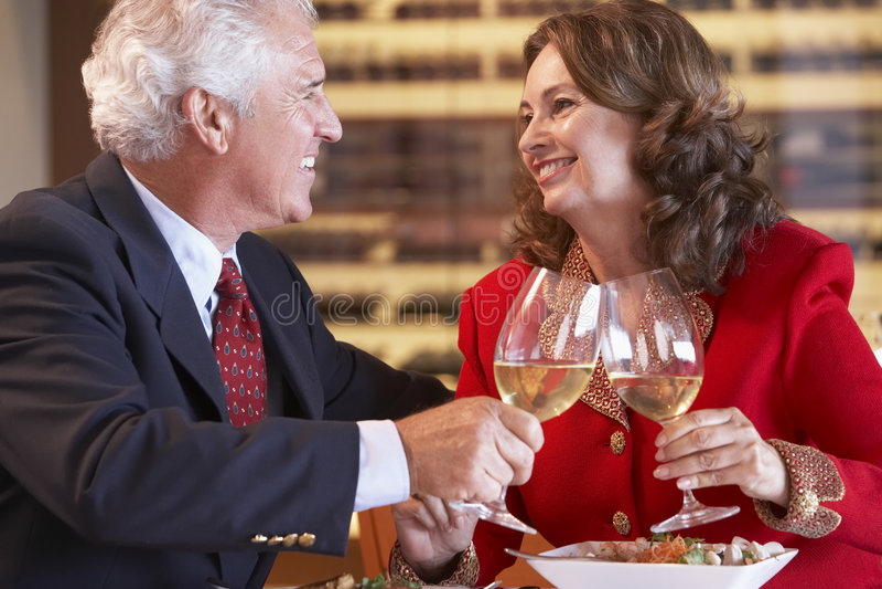 Pares que comen la cena y que beben el vino junto fotos de archivo