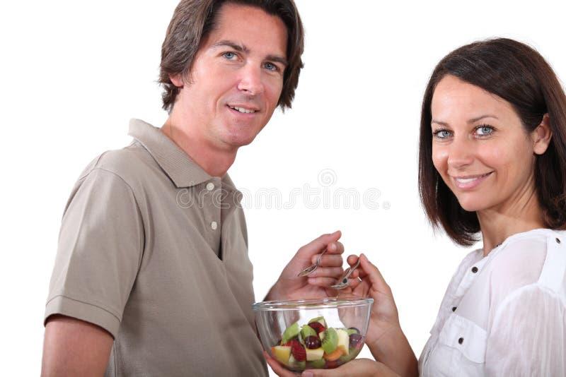 Pares que comen la ensalada de fruta imágenes de archivo libres de regalías