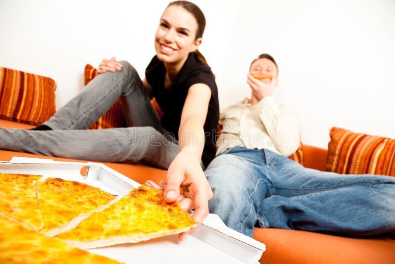 Pares que comen pizza en el sofá imagenes de archivo