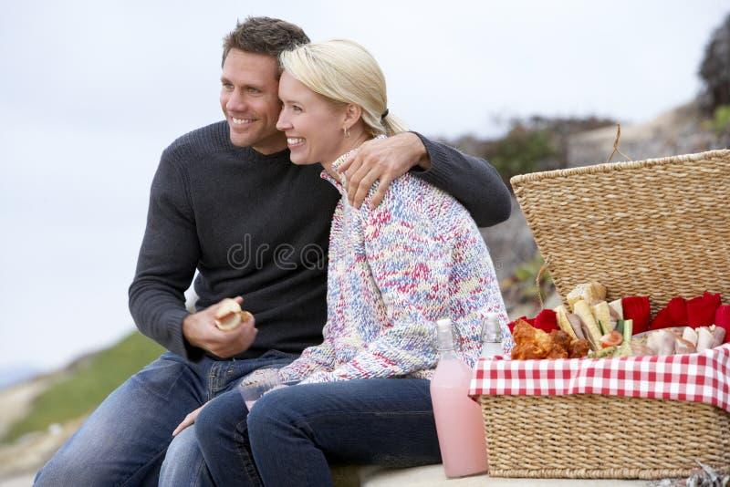 Pares que comen una comida del fresco del Al en la playa foto de archivo