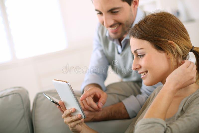 Pares que comparam smartphones em casa imagens de stock