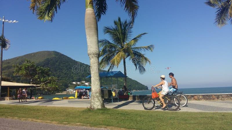 Pares que completan un ciclo a lo largo de la costa de Caraguatatuba imagen de archivo libre de regalías