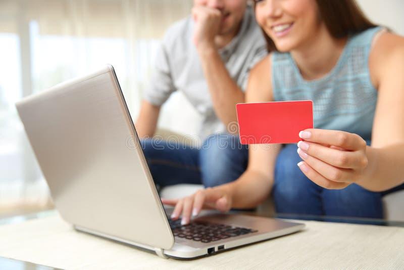 Pares que compram em linha com cartão de banco imagem de stock