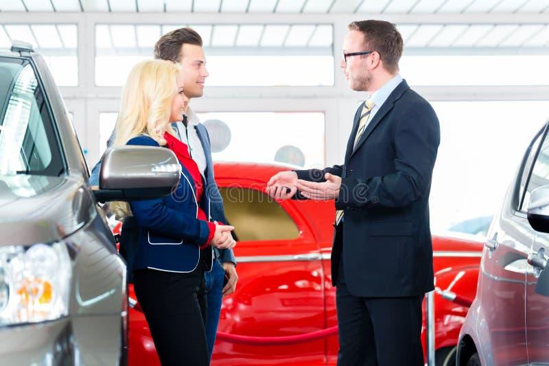 Pares que compram o carro novo no auto negócio imagem de stock