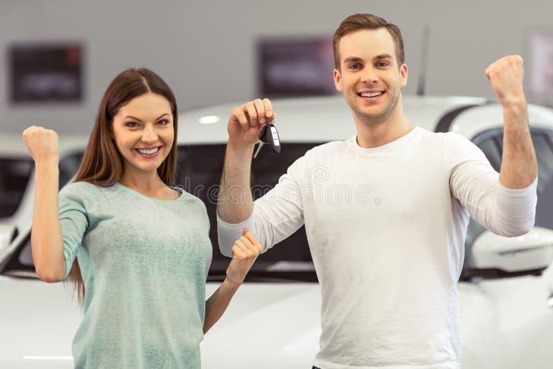 Pares que compram um carro imagens de stock