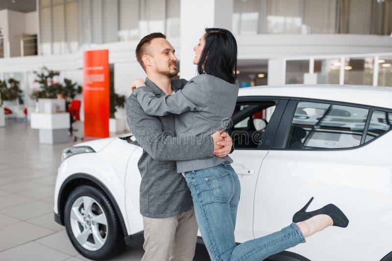 Pares que compran el nuevo abrazo del coche, del hombre y de la mujer fotografía de archivo