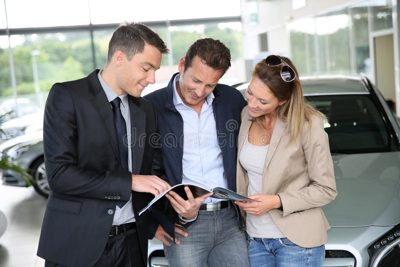 Pares que compran el nuevo coche con el vendedor de coches foto de archivo