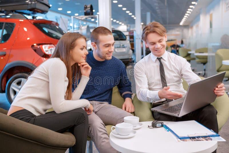 Pares que comunicam-se com o vendedor na sala de exposições imagem de stock royalty free