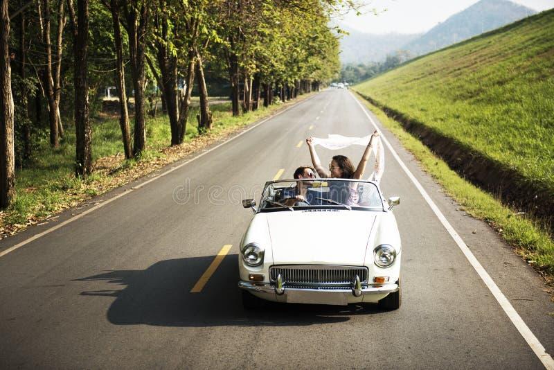 Pares que conducen un coche que viaja en viaje por carretera junto fotos de archivo libres de regalías