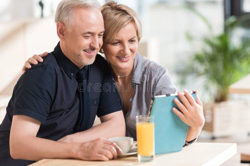 Pares que consideran algo la tableta y la sonrisa foto de archivo