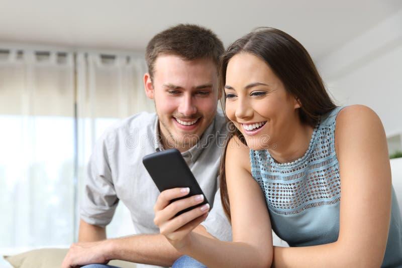 Pares que consultam um telefone celular em casa fotos de stock