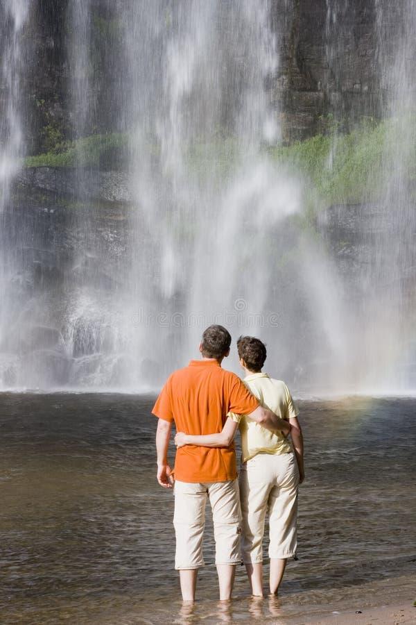 Pares que contemplam uma cachoeira imagens de stock royalty free