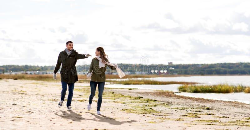 Pares que correm ao longo da praia do outono imagem de stock royalty free