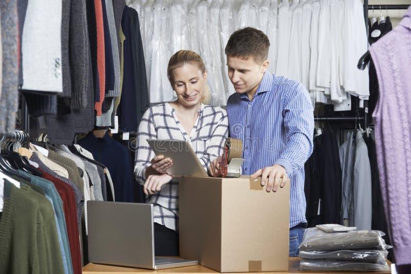 Pares que correm bens em linha da embalagem da loja de roupa para a expedição foto de stock royalty free