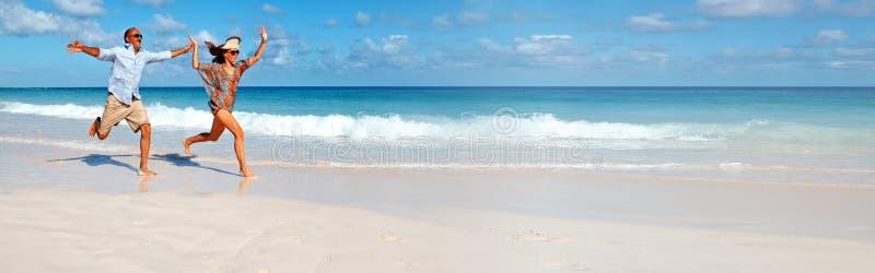 Pares que correm na praia imagens de stock royalty free