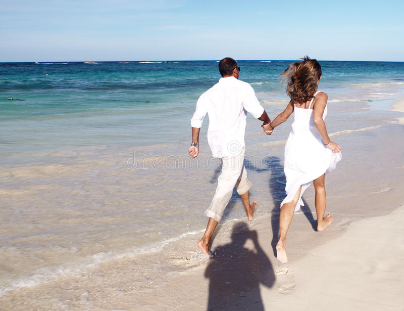 Pares que corren en la playa imagen de archivo libre de regalías
