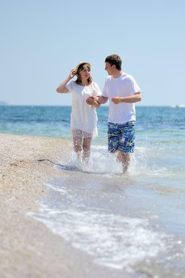 Pares que corren en una playa arenosa imagenes de archivo