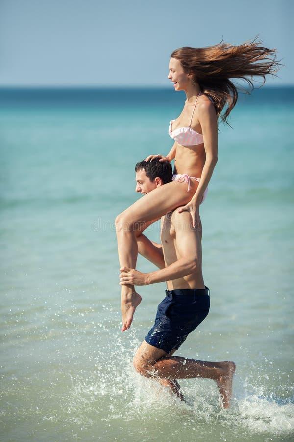Pares que corren en una playa tropical. Vacaciones fotografía de archivo