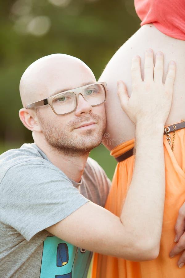 Pares que cuentan con embarazo, al aire libre fotografía de archivo