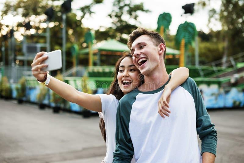 Pares que datam a apreciação do parque de diversões que abraça o conceito imagem de stock royalty free