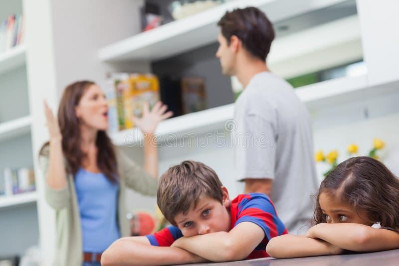 Pares que discutem atrás de suas crianças imagem de stock