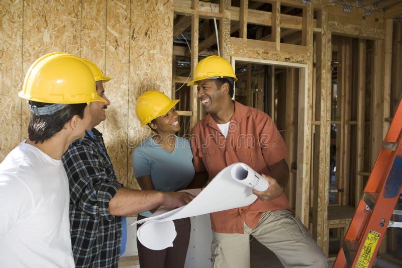 Pares que discutem planos da construção com os contratantes foto de stock royalty free