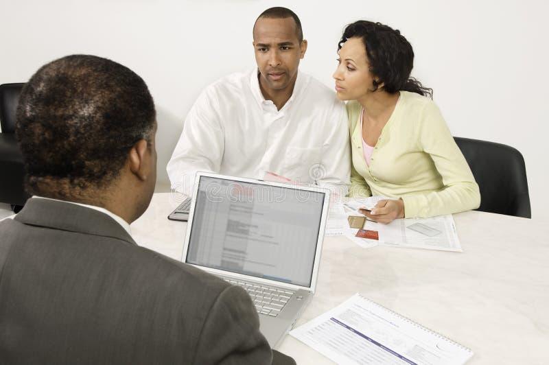 Pares que discutem planos financeiros com o conselheiro masculino imagens de stock royalty free