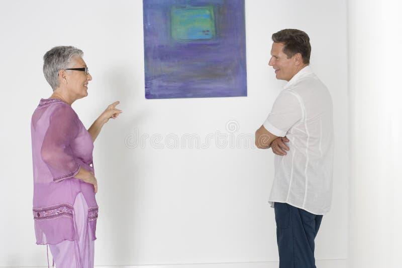 Pares que discutem sobre a pintura em Art Gallery imagens de stock